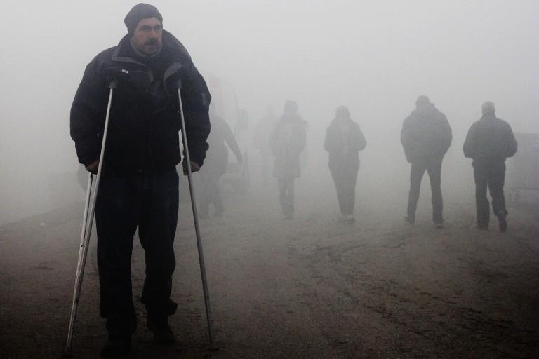 00020 vàris refugiats caminen entre la boira en la que s'ha despertat avui el camapent d' Idomeni